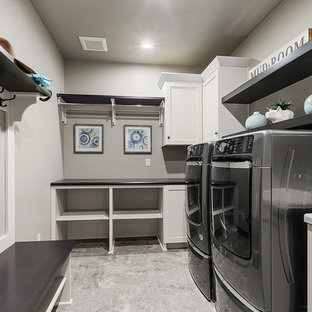 This is an example of a large traditional l-shaped utility room in Other with white cabinets, grey walls, vinyl flooring, a side by side washer and dryer, grey floors and shaker cabinets.
