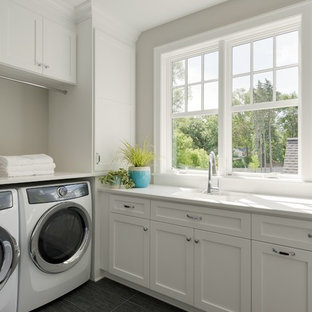 Example of a classic gray floor dedicated laundry room design in Minneapolis with an undermount sink, shaker cabinets, white cabinets, white countertops and gray walls