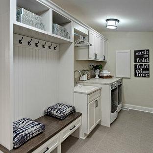 Idéer för små lantliga linjära grovkök, med en nedsänkt diskho, vita skåp, laminatbänkskiva, beige väggar, klinkergolv i porslin, en tvättmaskin och torktumlare bredvid varandra och luckor med infälld panel