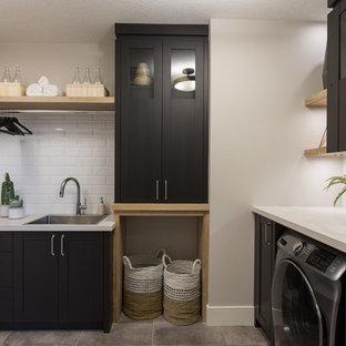 Immagine di una grande sala lavanderia country con lavello da incasso, ante in stile shaker, ante nere, top in laminato, pareti bianche, pavimento con piastrelle in ceramica, lavasciuga, pavimento grigio e top grigio