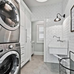 Foto på en lantlig linjär tvättstuga, med luckor med infälld panel, vita skåp, en tvättpelare och grått golv