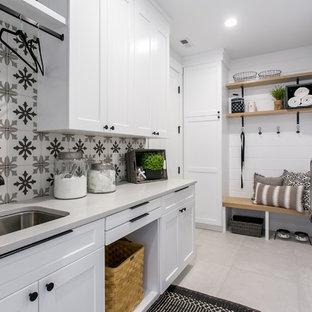 Inredning av en lantlig vita vitt tvättstuga, med en undermonterad diskho, skåp i shakerstil, vita skåp, vita väggar, en tvättmaskin och torktumlare bredvid varandra och grått golv
