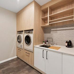 Ispirazione per una sala lavanderia minimalista di medie dimensioni con lavello sottopiano, top in superficie solida, pavimento in sughero e lavatrice e asciugatrice affiancate