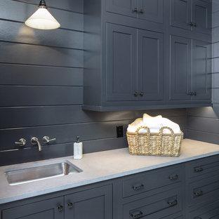Ispirazione per una lavanderia multiuso classica di medie dimensioni con ante blu, top in cemento, pareti blu, pavimento con piastrelle in ceramica, lavatrice e asciugatrice affiancate, pavimento bianco e top beige