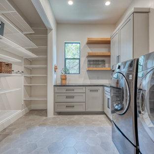 Esempio di una sala lavanderia moderna di medie dimensioni con ante in stile shaker, ante grigie, top in saponaria, pareti beige, pavimento in cemento, lavatrice e asciugatrice affiancate, pavimento grigio e top nero