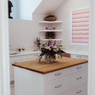 Inspiration för stora klassiska u-formade vitt grovkök, med en undermonterad diskho, skåp i shakerstil, vita skåp, bänkskiva i kvarts, vitt stänkskydd, stänkskydd i porslinskakel, grå väggar, klinkergolv i porslin, en tvättmaskin och torktumlare bredvid varandra och grått golv