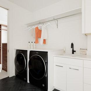 Idéer för att renovera en funkis vita l-formad vitt tvättstuga enbart för tvätt, med en undermonterad diskho, vita skåp, bänkskiva i kvartsit, vita väggar och en tvättmaskin och torktumlare bredvid varandra