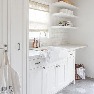 Foto di una lavanderia country con lavello stile country, ante in stile shaker, ante bianche, pareti bianche, pavimento grigio e top bianco