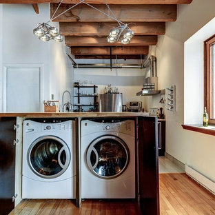 Inspiration for a small industrial laundry cupboard in Montreal with a side-by-side washer and dryer, flat-panel cabinets, medium wood cabinets, wood benchtops, white walls and medium hardwood floors.