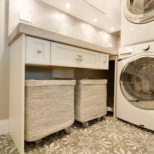 Esempio di una piccola lavanderia multiuso chic con ante bianche, top in marmo, pareti grigie, pavimento in cemento, lavatrice e asciugatrice a colonna, pavimento grigio, top grigio e ante con riquadro incassato