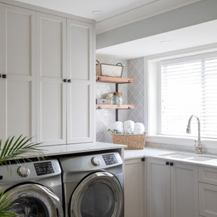 This is an example of a country l-shaped dedicated laundry room in Vancouver with shaker cabinets, white cabinets, white benchtop, a double-bowl sink, a side-by-side washer and dryer and multi-coloured floor.