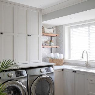 Bild på en lantlig vita l-formad vitt tvättstuga enbart för tvätt, med skåp i shakerstil, vita skåp, en dubbel diskho, en tvättmaskin och torktumlare bredvid varandra och flerfärgat golv