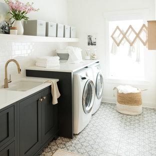 Ispirazione per una sala lavanderia chic con lavello sottopiano, ante in stile shaker, ante nere, pareti bianche, lavatrice e asciugatrice affiancate, pavimento multicolore e top bianco