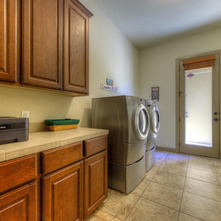 Immagine di una sala lavanderia contemporanea con ante con bugna sagomata, ante in legno bruno, top piastrellato, pareti grigie, pavimento con piastrelle in ceramica e lavatrice e asciugatrice affiancate