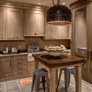 Idéer för att renovera en stor rustik u-formad tvättstuga enbart för tvätt, med en rustik diskho, skåp i mellenmörkt trä, skåp i shakerstil och en tvättmaskin och torktumlare bredvid varandra