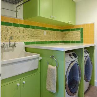 Ispirazione per una sala lavanderia minimal di medie dimensioni con lavatoio, ante lisce, ante verdi, top in quarzo composito, pareti bianche, pavimento in cemento, lavatrice e asciugatrice affiancate, pavimento grigio e top bianco