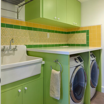 Dedicated laundry room - mid-sized contemporary single-wall concrete floor and gray floor dedicated laundry room idea in San Francisco with an utility sink, flat-panel cabinets, green cabinets, quartz countertops, white walls, a side-by-side washer/dryer and white countertops