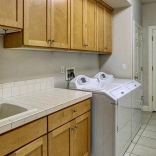 Esempio di una lavanderia multiuso stile americano di medie dimensioni con lavello da incasso, ante con riquadro incassato, top piastrellato, pareti grigie, pavimento in gres porcellanato, lavatrice e asciugatrice affiancate e ante in legno scuro
