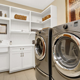 Elegant beige floor dedicated laundry room photo in New York with a farmhouse sink, shaker cabinets, white cabinets, beige walls, a side-by-side washer/dryer and white countertops