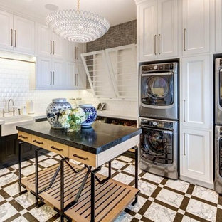 Expansive transitional l-shaped dedicated laundry room in Orange County with a farmhouse sink, white cabinets, a stacked washer and dryer, recessed-panel cabinets, solid surface benchtops, white walls, porcelain floors and multi-coloured floor.
