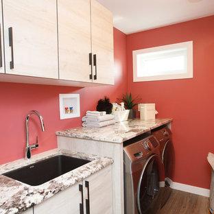Ispirazione per una sala lavanderia contemporanea con lavello sottopiano, ante lisce, ante in legno chiaro, pareti rosse, lavatrice e asciugatrice affiancate, top multicolore, parquet scuro e pavimento marrone