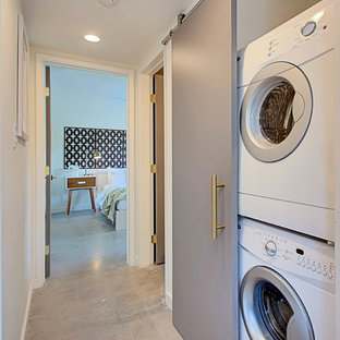 Laundry closet - small 1950s single-wall concrete floor laundry closet idea in Phoenix with white walls and a stacked washer/dryer