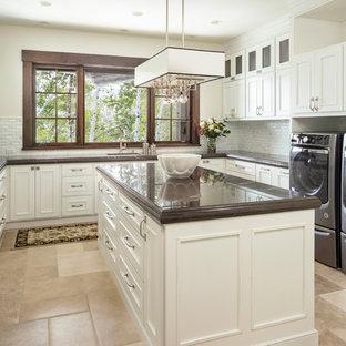 Bild på en stor vintage bruna u-formad brunt tvättstuga enbart för tvätt, med en undermonterad diskho, luckor med infälld panel, vita skåp, beige väggar, en tvättmaskin och torktumlare bredvid varandra, beiget golv och travertin golv