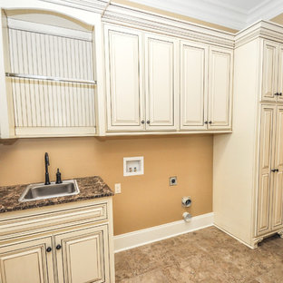 Inspiration for a large traditional l-shaped dedicated laundry room in New Orleans with a drop-in sink, raised-panel cabinets, distressed cabinets, granite benchtops, beige walls, ceramic floors, a side-by-side washer and dryer and beige floor.