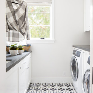 Coastal galley multicolored floor dedicated laundry room photo in Los Angeles with an undermount sink, recessed-panel cabinets, white cabinets, white walls and gray countertops