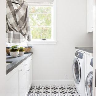 Idee per una sala lavanderia stile marinaro con lavello sottopiano, ante con riquadro incassato, ante bianche, pareti bianche, lavatrice e asciugatrice affiancate, pavimento multicolore e top grigio