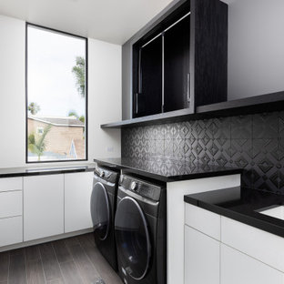 Example of a small trendy beige floor dedicated laundry room design in San Diego with an integrated sink, white backsplash, white walls, a side-by-side washer/dryer and black countertops