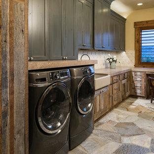 Immagine di un'ampia sala lavanderia rustica con lavello stile country, ante in legno scuro, lavatrice e asciugatrice affiancate, pavimento grigio, top marrone, ante in stile shaker e pareti beige