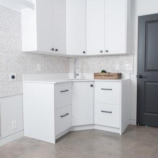 Immagine di una sala lavanderia industriale di medie dimensioni con lavello sottopiano, ante lisce, ante bianche, top in quarzite, pareti bianche, pavimento in cemento, lavatrice e asciugatrice affiancate, pavimento grigio e top bianco