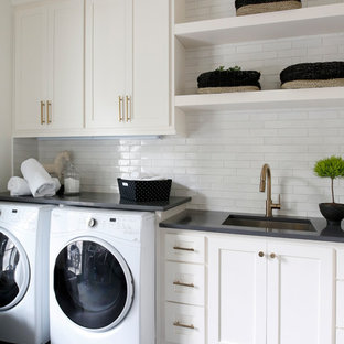 Beach style single-wall separated utility room in Nashville with a submerged sink, shaker cabinets, white cabinets, white walls, a side by side washer and dryer, grey floors and black worktops.
