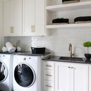Ispirazione per una sala lavanderia stile marino con lavello sottopiano, ante in stile shaker, ante bianche, pareti bianche, lavatrice e asciugatrice affiancate, pavimento grigio e top nero