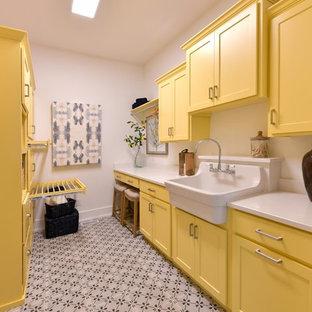 Inspiration för en vintage vita vitt tvättstuga enbart för tvätt, med en rustik diskho, skåp i shakerstil, gula skåp, vita väggar och flerfärgat golv
