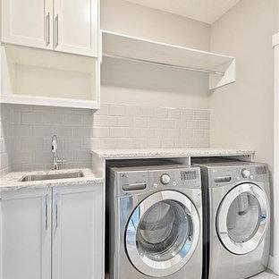 Idéer för mellanstora funkis linjära tvättstugor enbart för tvätt, med skåp i shakerstil, vita skåp, grönt stänkskydd, stänkskydd i tunnelbanekakel, en undermonterad diskho, granitbänkskiva, grå väggar, klinkergolv i keramik och en tvättmaskin och torktumlare bredvid varandra