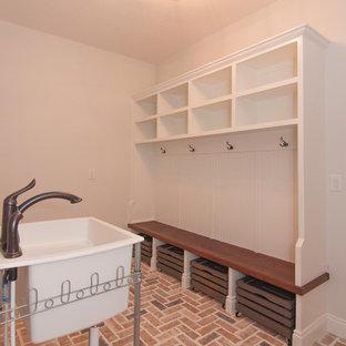 Ispirazione per una grande lavanderia multiuso american style con lavatoio, ante a filo, ante bianche, pareti bianche, pavimento in mattoni, lavatrice e asciugatrice affiancate, pavimento multicolore e top bianco