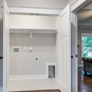 Inspiration for a large country single-wall medium tone wood floor and brown floor laundry closet remodel in Richmond with gray walls and a side-by-side washer/dryer