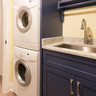 Неиссякаемый источник вдохновения для домашнего уюта: маленькая прямая универсальная комната в морском стиле с врезной раковиной, фасадами в стиле шейкер, синими фасадами, мраморной столешницей, белым фартуком, фартуком из мрамора, желтыми стенами, паркетным полом среднего тона, с сушильной машиной на стиральной машине, коричневым полом и белой столешницей