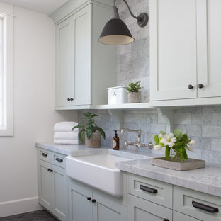 Photo of a large rural galley separated utility room in Phoenix with a belfast sink, shaker cabinets, green cabinets, marble worktops, white walls, brick flooring, a side by side washer and dryer, black floors and grey worktops.