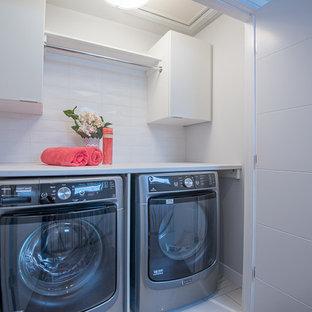 Esempio di una piccola lavanderia contemporanea con ante lisce, ante bianche, top in superficie solida, pareti bianche, lavatrice e asciugatrice affiancate e pavimento bianco