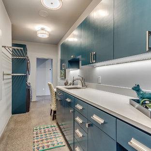 Immagine di una lavanderia multiuso design di medie dimensioni con lavello sottopiano, ante lisce, ante blu, pareti bianche, pavimento in cemento, lavatrice e asciugatrice a colonna, top in quarzo composito, pavimento beige e top bianco