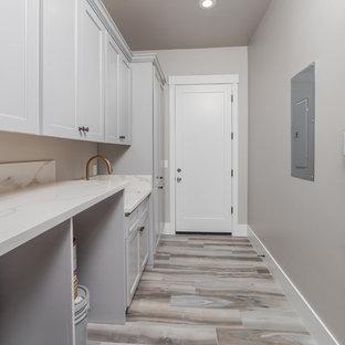 Foto på en stor funkis grå linjär tvättstuga enbart för tvätt och med garderob, med en integrerad diskho, släta luckor, grå skåp, marmorbänkskiva, grå väggar, ljust trägolv och grått golv