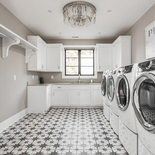 Inspiration for a large mediterranean separated utility room in Indianapolis with white cabinets, concrete flooring, a side by side washer and dryer and multi-coloured floors.