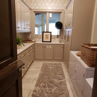 Idee per una grande lavanderia multiuso mediterranea con ante in stile shaker, ante grigie, top in marmo, paraspruzzi grigio, paraspruzzi con piastrelle in ceramica, pareti grigie, lavatrice e asciugatrice affiancate, pavimento beige e top bianco