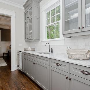 Immagine di una lavanderia stile americano di medie dimensioni con lavello a vasca singola, ante di vetro, ante grigie, top in marmo, pareti grigie e pavimento in legno massello medio