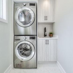 Inspiration för små moderna linjära vitt tvättstugor enbart för tvätt, med en undermonterad diskho, släta luckor, grå skåp, bänkskiva i kvarts, beige stänkskydd, stänkskydd i keramik, vita väggar, klinkergolv i porslin, en tvättpelare och vitt golv