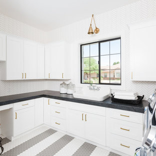 Inspiration for a mediterranean u-shaped multicolored floor dedicated laundry room remodel in Phoenix with shaker cabinets, white cabinets, white walls and gray countertops