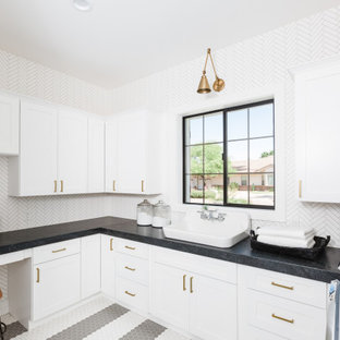 Inspiration for a transitional u-shaped dedicated laundry room in Phoenix with a drop-in sink, shaker cabinets, white cabinets, mosaic tile splashback, a side-by-side washer and dryer, multi-coloured floor and black benchtop.